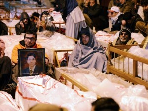 Shia Muslims demonstrate by sitting amongst the bodies of blast victims two days after the attacks.PHOTO: AFP
